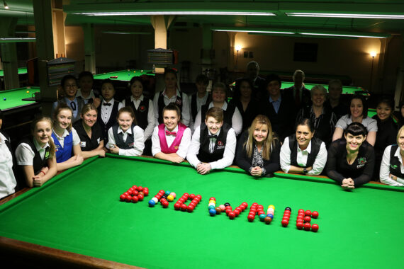 Group of players stood next to snooker table with balls shaped to say 'Brownie'